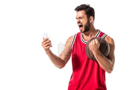 Photo pour Joueur de basket-ball criant avec la bille utilisant le smartphone isolated on White - image libre de droit