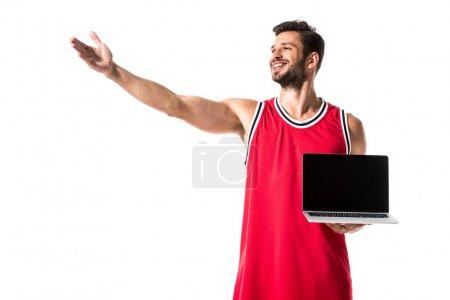 Photo pour Joueur de basket-ball dans l'uniforme avec l'ordinateur portatif et la main tendue d'isolement sur le blanc - image libre de droit
