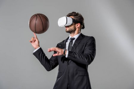 Photo for Businessman in Virtual reality headset spinning on finger basketball on grey - Royalty Free Image