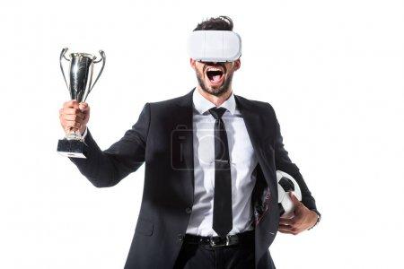 Photo pour Homme d'affaires excité en réalité virtuelle casque avec ballon de football et coupe trophée isolé sur blanc - image libre de droit