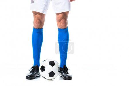 Photo pour Vue cultivée de joueur de football restant près du ballon d'isolement sur le blanc - image libre de droit
