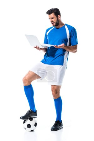Photo for Confused soccer player using laptop and standing on ball Isolated On White - Royalty Free Image