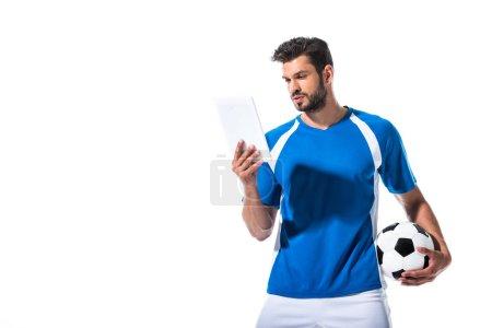 Photo pour Joueur de football beau avec le bille utilisant la tablette numérique d'isolement sur le blanc - image libre de droit