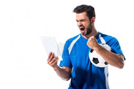 Photo pour Beau joueur de football avec ballon et tablette numérique acclamant isolé sur blanc - image libre de droit
