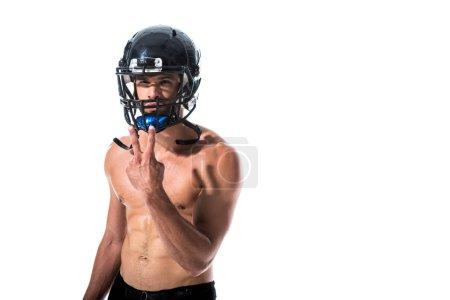 Photo pour Joueur de football américain torse nu dans le casque faisant le signe de paix d'isolement sur le blanc - image libre de droit