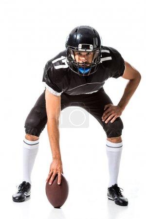 Photo pour Joueur américain de football retenant la bille et regardant l'appareil-photo d'isolement sur le blanc - image libre de droit