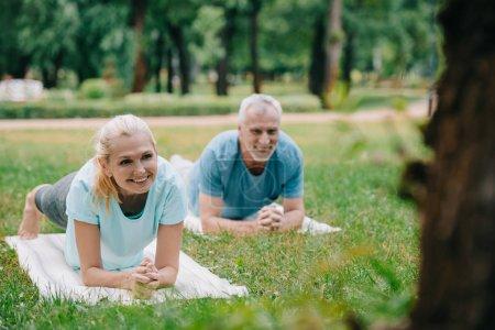 Photo pour Foyer sélectif de sourire l'homme et la femme mûrs faisant l'exercice de planche tout en pratiquant le yoga dans le stationnement - image libre de droit