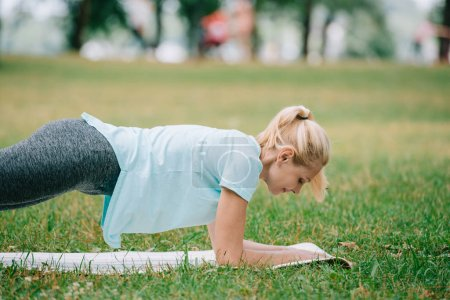 Photo pour Attractive mature woman doing plank exercise while racticing yoga on green lawn in park - image libre de droit