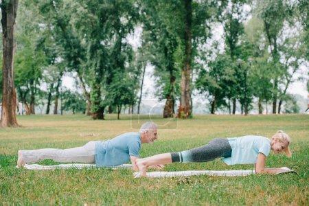 Photo pour Homme et femme mûrs faisant l'exercice de planche tout en pratiquant le yoga sur des tapis de yoga dans le stationnement - image libre de droit