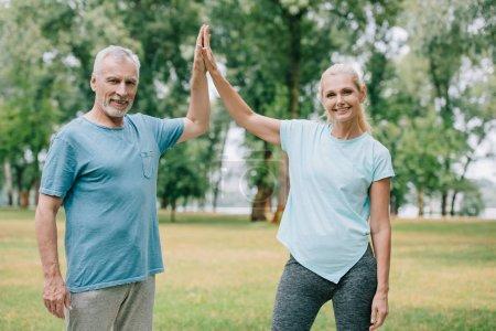 Photo pour Sportif gai et sportive donnant cinq tout en souriant à la caméra - image libre de droit