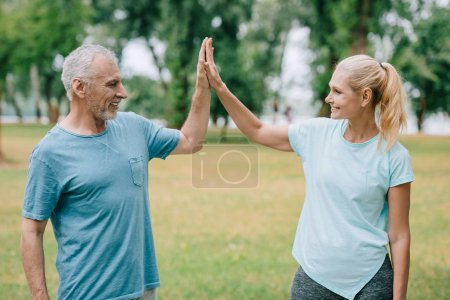 mature, cheerful sportsman and sportswoman giving high five and looking at each other