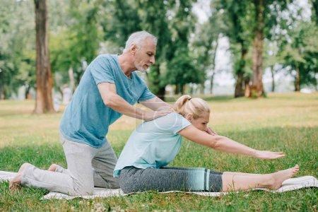 Photo pour L'homme mûr beau aidant la femme pratiquant la pose de yoga sur la pelouse en stationnement - image libre de droit