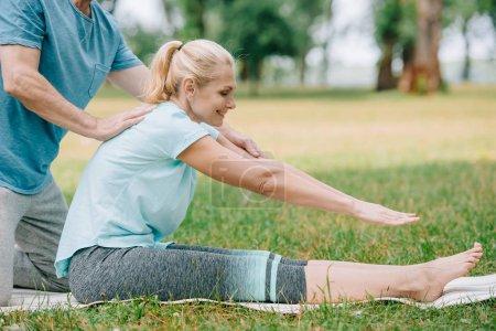 Photo pour Vue partielle de l'homme aidant la femme de sourire pratiquant le yoga sur la pelouse en stationnement - image libre de droit