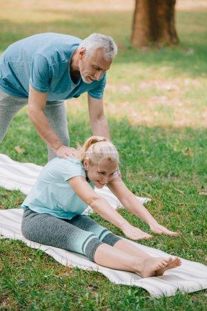 Photo pour L'homme mûr beau aidant la femme de sourire pratiquant la pose de yoga d'étirement sur la pelouse - image libre de droit