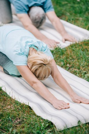 Photo pour Homme et femme mûrs pratiquant le yoga de relaxation pose sur des tapis de yoga dans le stationnement - image libre de droit