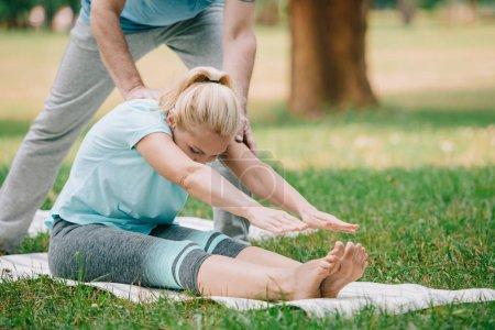 Photo pour Vue recadrée de l'homme aidant la femme pratiquant la pose de yoga dans le stationnement - image libre de droit