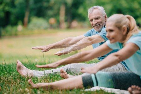 Photo pour Foyer sélectif de l'homme et de la femme mûrs sur des tapis de yoga pratiquant le yoga dans le stationnement - image libre de droit