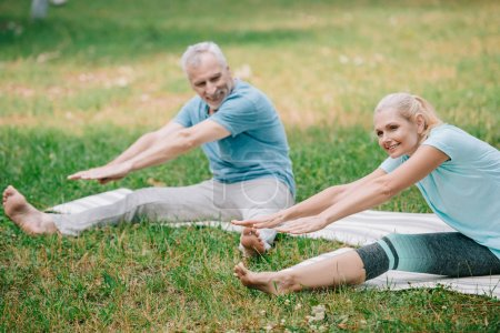 Photo for Smiling man and woman practicing stretching yoga poses while sitting on yoga mats - Royalty Free Image