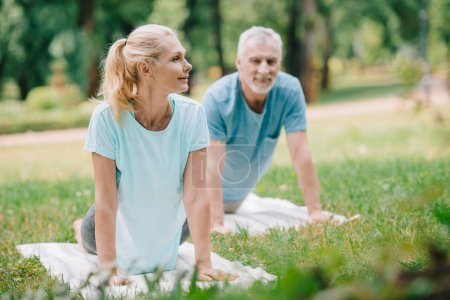 selective focus of smiling, mature man and woman practicing yoga on yoga mats in park