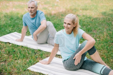 Photo pour Homme et femme mûrs souriant tout en pratiquant le yoga dans le stationnement - image libre de droit