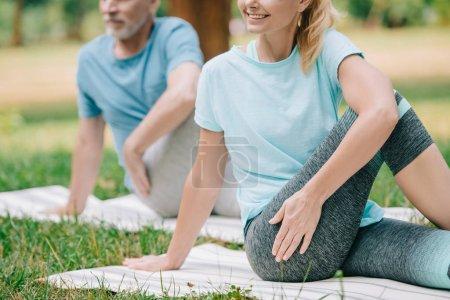 Photo pour Vue partielle de l'homme et de la femme mûrs pratiquant le yoga sur la pelouse en stationnement - image libre de droit