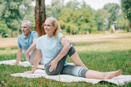 Photo pour Homme et femme mûrs de sourire pratiquant le yoga tout en s'asseyant sur des tapis de yoga dans le stationnement - image libre de droit