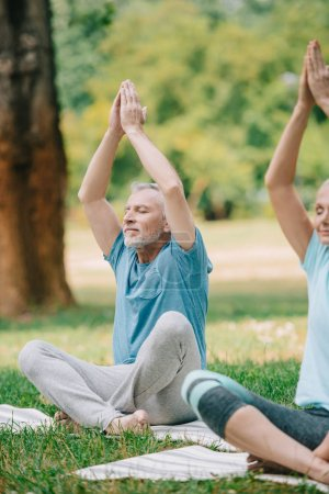 mature man and woman meditating in lotus poses with closed eyes in park