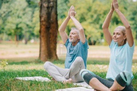 Photo pour Homme mûr et femme méditant tout en s'asseyant dans des poses de lotus sur des tapis de yoga dans le stationnement - image libre de droit