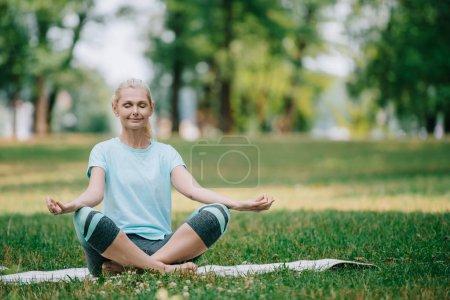 Photo pour Belle femme mûre méditant avec les yeux fermés tout en s'asseyant dans la pose de lotus sur la pelouse dans le stationnement - image libre de droit