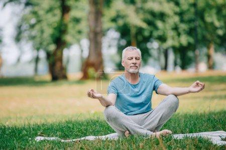Photo pour Bel homme mûr méditant tout en s'asseyant dans la pose de lotus dans le stationnement - image libre de droit