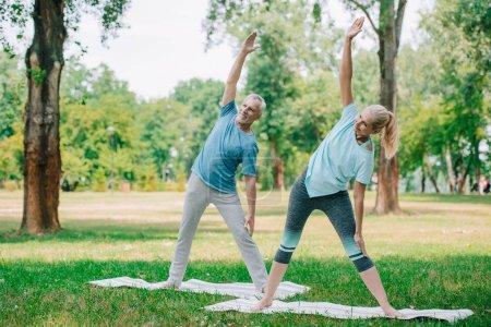 Photo pour Homme et femme souriants et mûrs restant dans des poses de guerrier tout en pratiquant le yoga dans le stationnement - image libre de droit