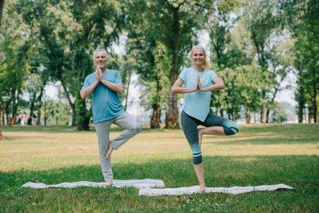 Photo pour Homme et femme mûrs de sourire restant dans des poses d'arbre tout en pratiquant le yoga dans le stationnement - image libre de droit