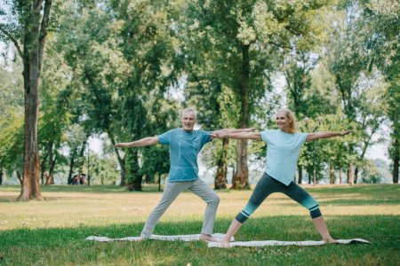Photo pour Smiling man and woman standing in yoga poses while practicing yoga in park - image libre de droit