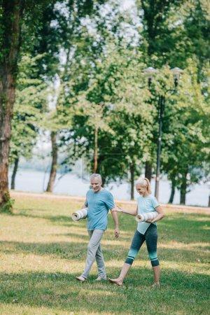 Photo pour Homme et femme mûrs joyeux marchant ensemble dans le stationnement tout en retenant des tapis de yoga - image libre de droit