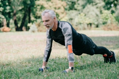 Photo for Handsome mature sportsman doing push ups with barbells on lawn in park - Royalty Free Image