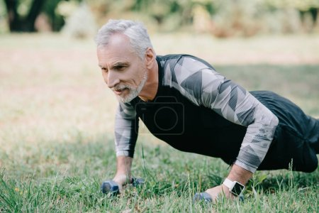 positive mature sportsman doing push ups with barbells on lawn in park