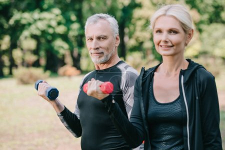 Photo for Smiling mature sportsman and sportswoman looking at camera while training with barbells in park - Royalty Free Image