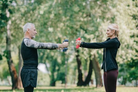 Photo for Side view of smiling mature sportsman and sportswoman training with barbells in park and looking at each other - Royalty Free Image