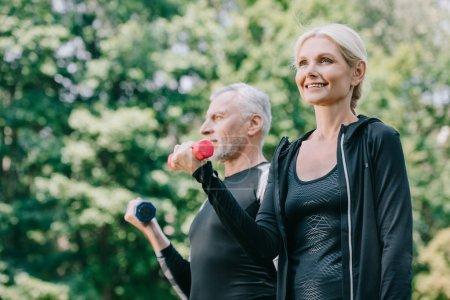 Photo pour Gai, sportif mature et sportif regardant loin tout en s'entraînant avec des cloches dans le parc - image libre de droit