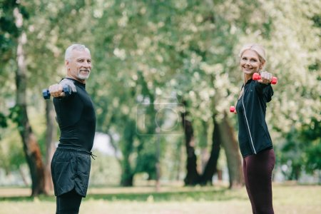 cheerful, mature sportsman and sportswoman training with dumbbells in park and smiling at camera