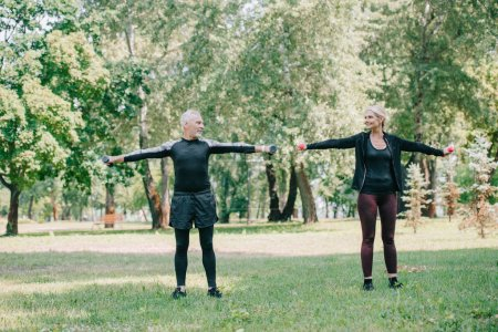 Photo for Mature sportsman and sportswoman looking at each other while training with barbells in park - Royalty Free Image
