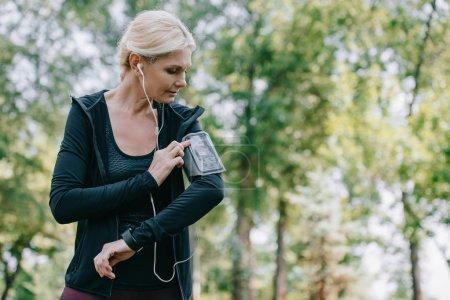 attractive, mature sportswoman listening music in earphones in park