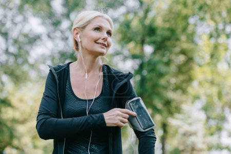 smiling mature sportswoman looking away while listening music in earphones