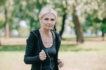 Photo for Beautiful mature sportswoman listening music in earphones while jogging in park - Royalty Free Image
