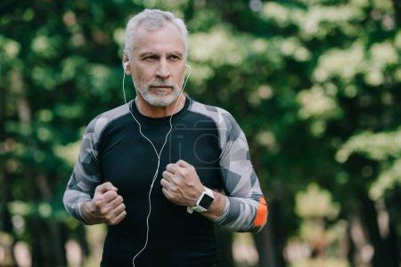 Photo pour Beau sportif mature écoutant de la musique dans les écouteurs tout en courant dans le parc - image libre de droit