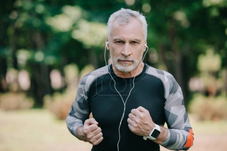 Photo for Confident mature sportsman listening music in earphones while jogging in park - Royalty Free Image