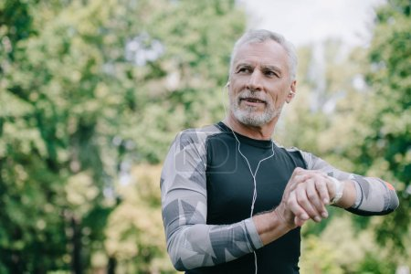 Photo for Smiling mature sportsman touching fitness tracker while listening music in earphones - Royalty Free Image