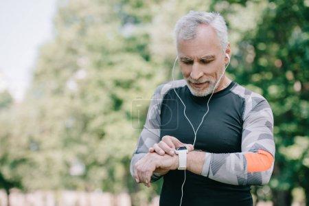 Photo pour Beau sportif mature regardant fitness suivi tout en écoutant de la musique dans les écouteurs - image libre de droit