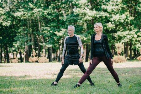 Photo pour Sportif mature et sportif s'entraînent ensemble dans un parc vert - image libre de droit