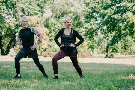 Photo for Cheerful, mature sportsman and sportswoman doing lunges exercises in park - Royalty Free Image